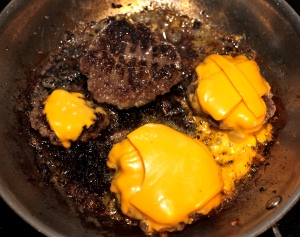 Now that the mustardy side is all happy, put American cheese all up on this burger b----- til melted and way too tasty and also kind of awful but so delicious (How rude! - Stephanie Tanner)